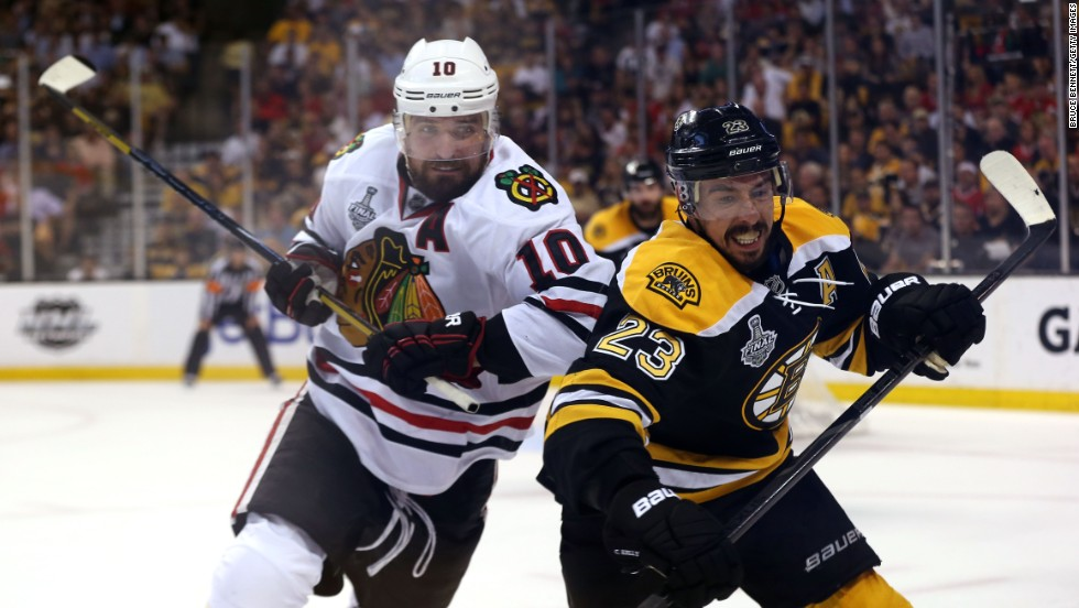 Patrick Sharp of the Chicago Blackhawks checks Chris Kelly of the Boston Bruins.