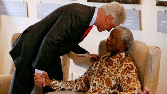 Former U.S. President Bill Clinton leans down to whisper to former South African President Nelson Mandela during a visit to the Nelson Mandela Foundation on July 19, 2007, in Johannesburg.