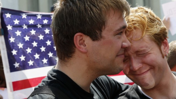 Michael Knaapen, left, and his husband, John Becker, react to the rulings in Washington.
