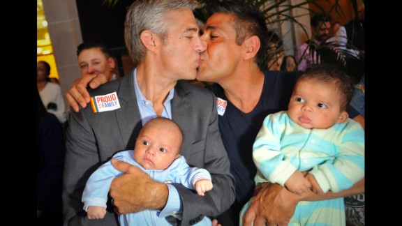 Chris Roe, left, and Roby Chavez celebrate while holding their soon-to-be-adopted children as the ruling is announced in San Francisco.