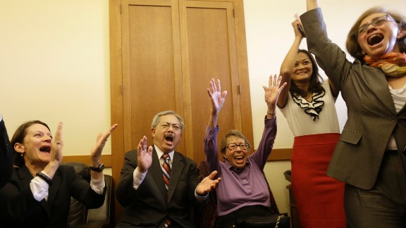 San Francisco Mayor Ed Lee, second from left, and Phyllis Lyon, center, celebrate at the mayor's office in San Francisco.