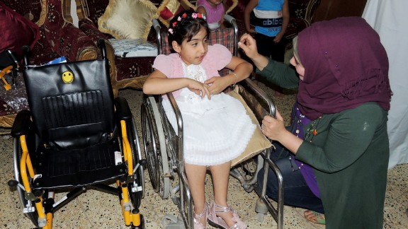 Noor al-Zahra Haider, who has spina bifida, receives a new pediatric wheelchair  from America this week in Baghdad.