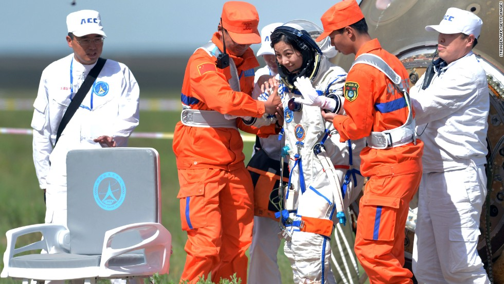 Wang Yaping (3rd R) is supported as she exits the spacecraft.  The successful mission was a major step toward China's goal of building a permanent space station by 2020.