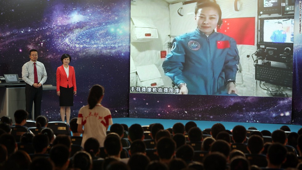 A girl at a Beijing school asks Chinese astrounaut Wang Yaping (Top R) questions as Wang delivers a lesson to students while orbiting in the Tiangong-1 space module on June 20.
