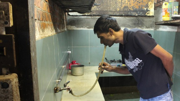 Saidur Rahman, a refugee from Bangladesh, drinks water from a hose in the slum of Ping Che, Hong Kong on June 25, 2013. Rahman and other asylum seekers in Hong Kong receive a housing allowance of $1,200 HKD ($155) a month, which barely covers rent for the most rudimentary housing.