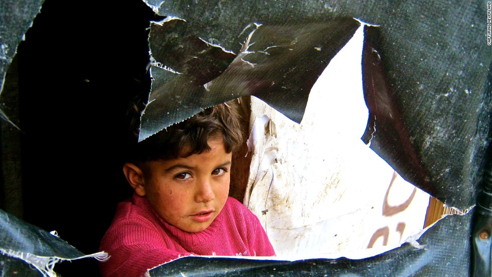 "Underprivileged children age 8 to 16 have captured striking images of kids whose lives mirror their own. It's a children's workshop called Capturing Neverland, founded by Sara Khazem, a Lebanese-American who wants to use art to help others. In this photo, titled ""Life Within Life,"" a boy with a dirty face stares through a ripped piece of tarp."