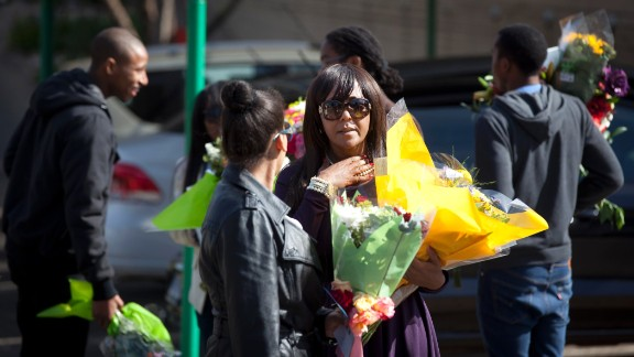 Mandela's granddaughter Ndileka Mandela and other family members collect flowers left by well-wishers on June 27.