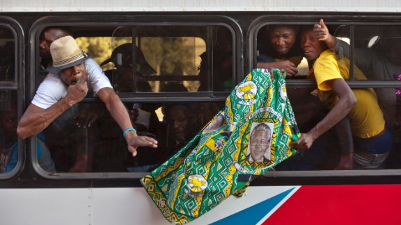 Members of the African National Congress Youth League wave a banner from their bus as they drive to join the gathering on June 27.