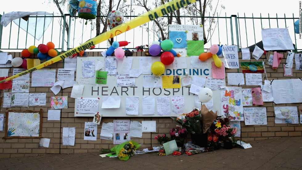 Messages, paintings, cards and flowers are posted to a wall outside the hospital on June 25.