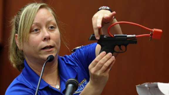 During the trial on June 25, crime scene technician Diana Smith shows the jury a gun that was collected as evidence.