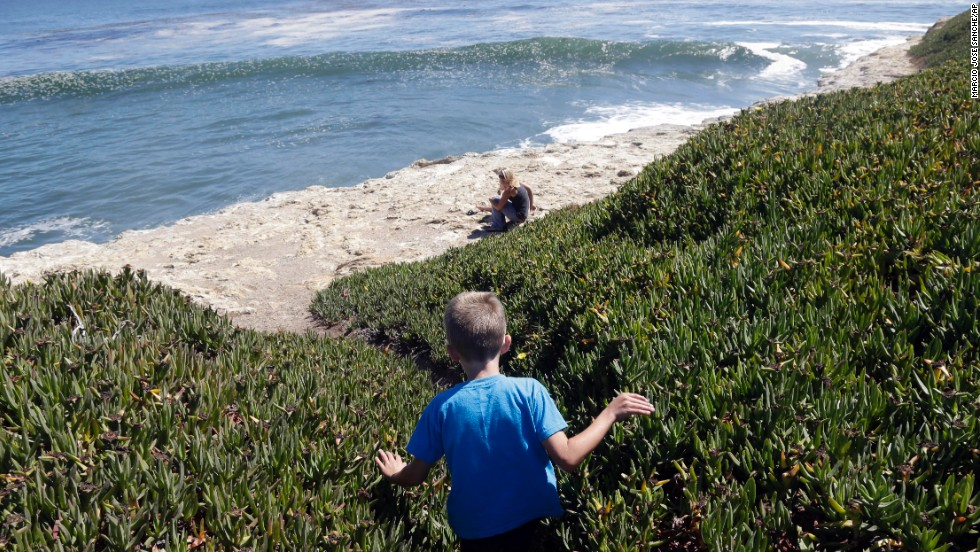 Bryson Hubbard, 7, walks down a path leading to a sea cliff as his mother Vanessa Singer waits for him on a hot day in Santa Cruz, California, on June 27.