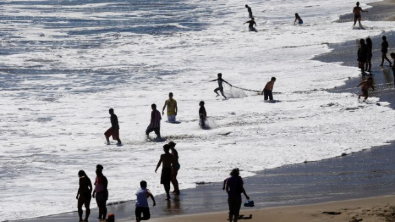 Beach-goers enjoy the surf at Natural Bridges in Santa Cruz on June 27.