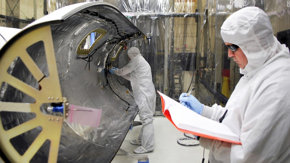 Technicians work on the payload fairing built to protect the IRIS spacecraft during launch aboard an Orbital Sciences Pegasus XL rocket.