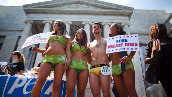 """PETA """"lettuce ladies"""" and a """"banana boy"""" prepare to serve vegan hotdogs to passers-by in Washington on July 11, 2012. Not afraid of showing a bit of skin, the animal rights organization is known for using controversial tactics to bring attention to its causes."""