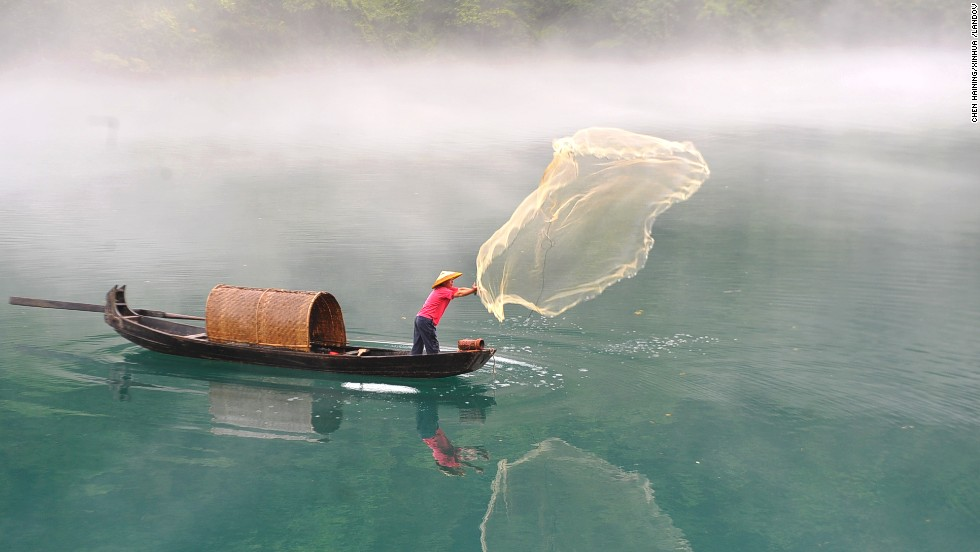 A fisherman casts a net on the fog-enveloped Xiaodongjiang River in Zixing, China, on Tuesday, June 25.