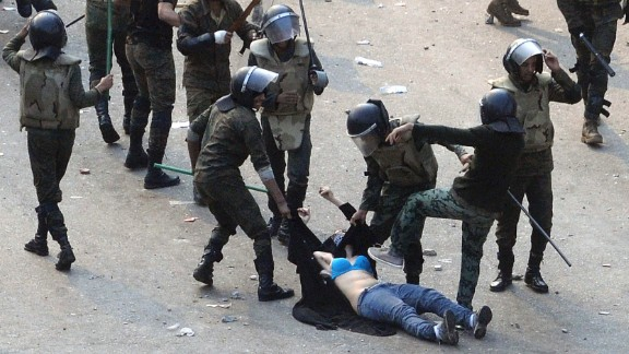 """Egyptian army soldiers beat a young woman during a protest at Tahrir Square in Cairo on December 17, 2011. The shocking image of the """"blue bra girl"""" became a symbol of the oppression and a rallying cry for several thousand Egyptian women."""
