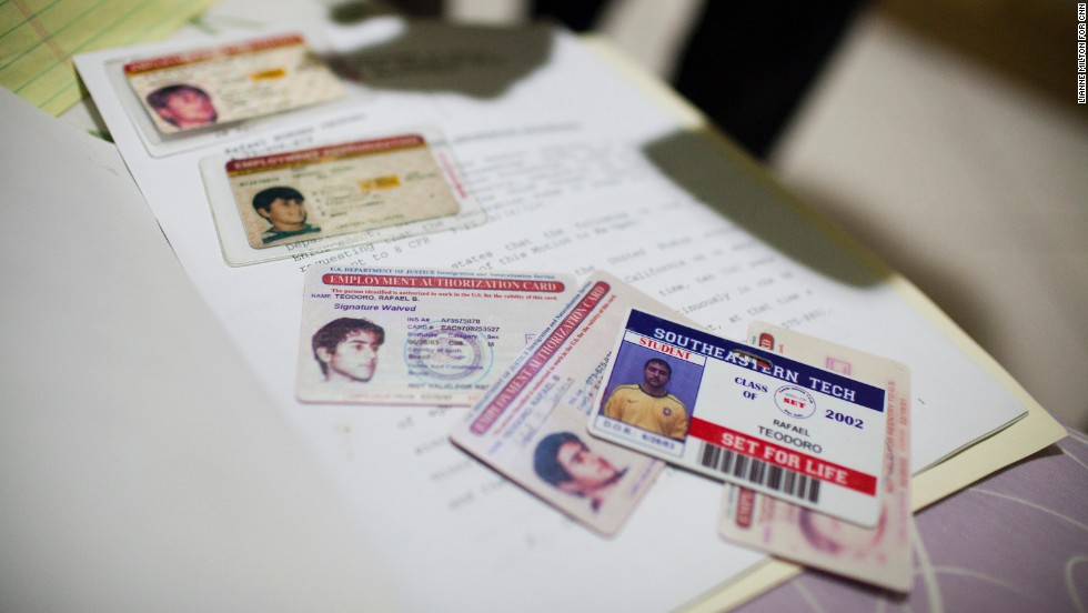Renata's brother Rafael, 29, shows his U.S. work authorization cards and a high school identification card at his home in Brazil.