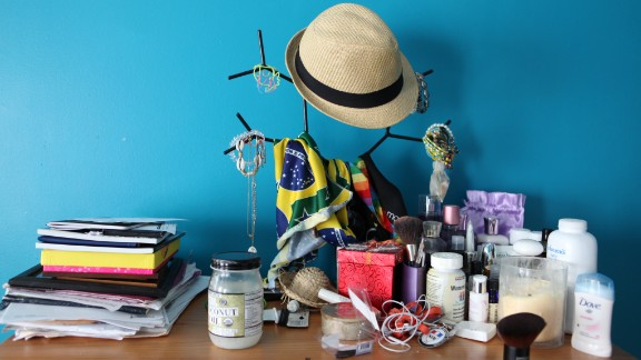 Personal items, make-up and a bandera of the flag of Brazil adorn a dresser in Renata's apartment in Boston.