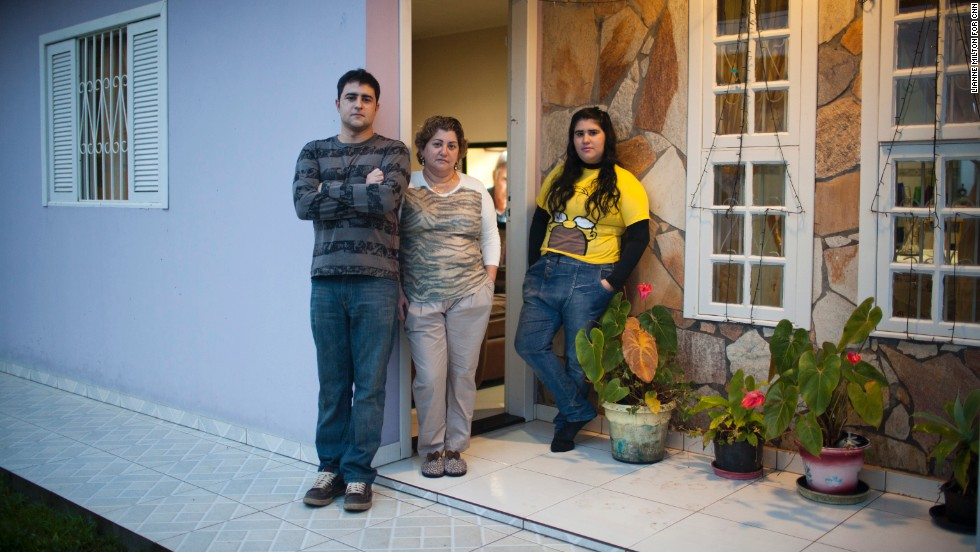 Renata would have to wait five years before she can begin petitioning for her family's return to the United States, but the process could take as long as seven years if an upcoming amendment passes that would further militarize the border. Here her brother, mother and sister pose outside their home in Brazil.