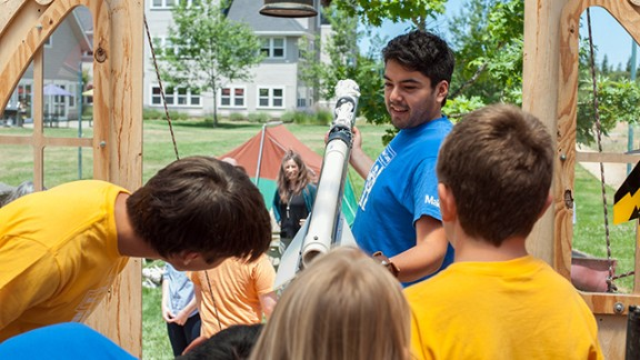 A Maker Media staffer shows off a potato air cannon to a group of kids. For safety reasons, they shoot ping-pong balls out of the cannon instead of potatoes.