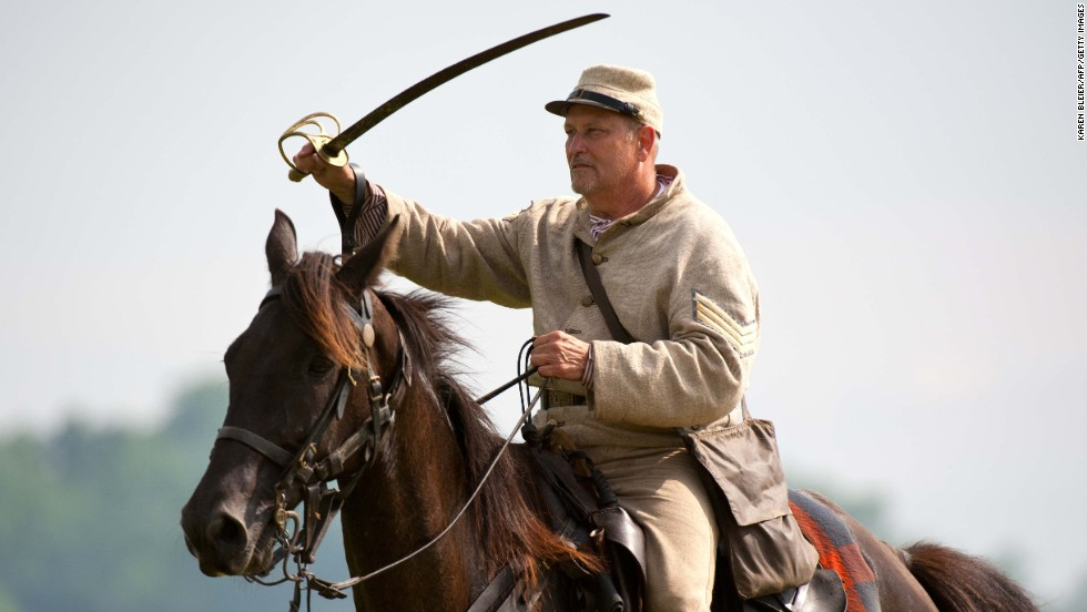 A Confederate sergeant waves his saber to rally troops during a reenactment. Another such event is planned next weekend.