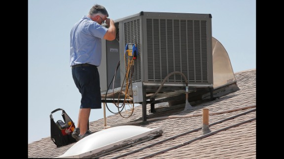 Michael Hawks, a warranty supervisor for an air conditioning company, wipes his brow while inspecting a unit in Phoenix on June 28.
