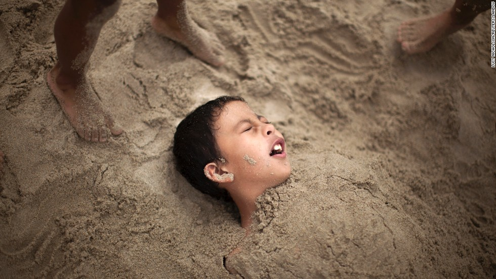 R.J. Hernandez, 8, of El Campo, Texas, is buried in sand as he tries to stay cool in Santa Monica on Friday, June 28.
