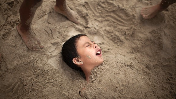 R.J. Hernandez, 8, of El Campo, Texas, is buried in sand as he tries to stay cool in Santa Monica on June 28.
