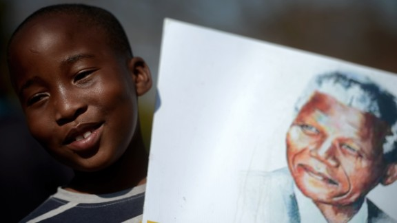 A child holds a portrait of Nelson Mandela in Pretoria, South Africa.