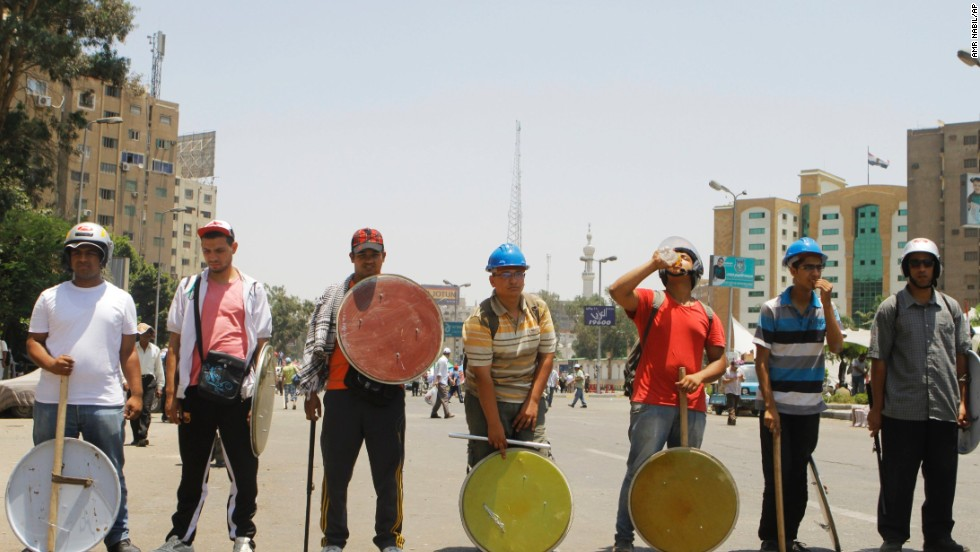 Morsy supporters, armed with sticks and shields, stand guard at their protest site in Cairo on June 29.