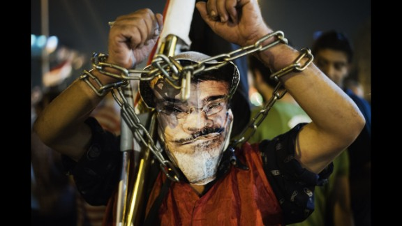 A chained protester wearing a picture of Morsy participates in an anti-government protest in Tahrir Square on Wednesday, June 26.
