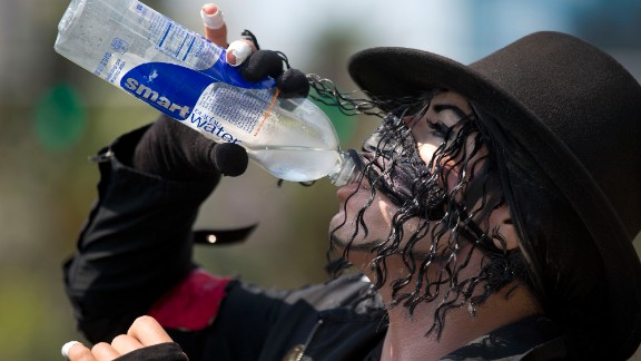 Michael Jackson impersonator Juan Carlos Gomez gulps down some water on Friday, June 28, during a break from posing for photos with tourists along the Las Vegas strip.