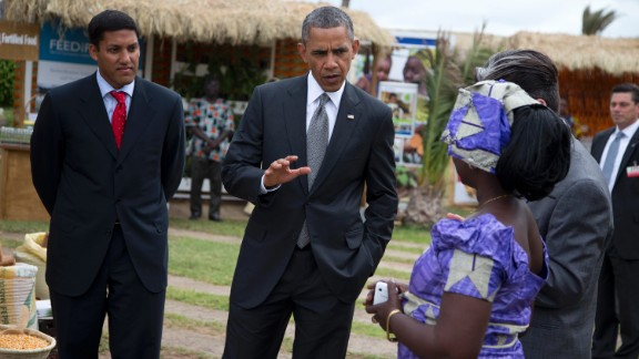 USAID administrator Rajiv Shah, left, looks on as Obama talks to Nimna Diayte, president of the Farmers Federation, during a food security expo on Friday, June 28, in Dakar, Senegal. Obama met with farmers, innovators, and entrepreneurs whose new methods and technologies are improving the lives of smallholder farmers throughout West Africa.