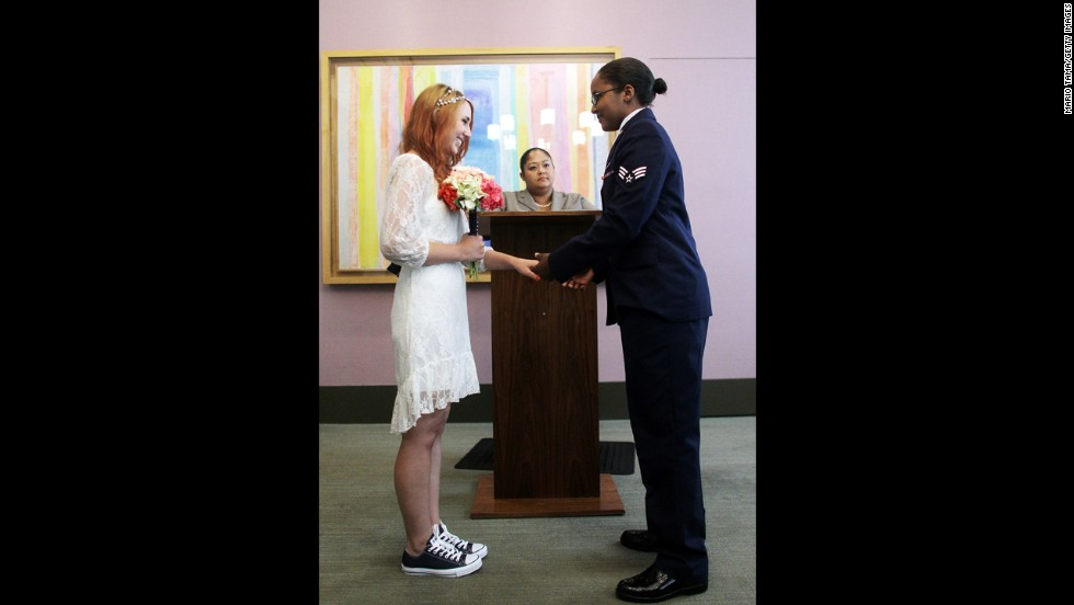 U.S. Air Force Senior Airman Shyla Smith, right, and Courtney Burdeshaw hold hands in the west chapel during their wedding ceremony at the Manhattan Marriage Bureau on Thursday, June 27.