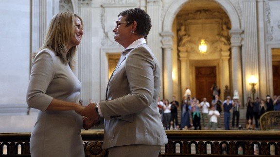 Sandy Stier, left, exchanges wedding vows with Kris Perry during a ceremony presided over by California Attorney General Kamala Harris at City Hall in San Francisco on Friday, June 28. Stier and Perry were two of the four lead plaintiffs in the U.S. Supreme Court case that overturned California