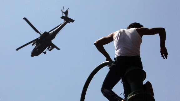 A protester watches an Apache helicopter as it flies over Tahrir Square on June 30. Morsy