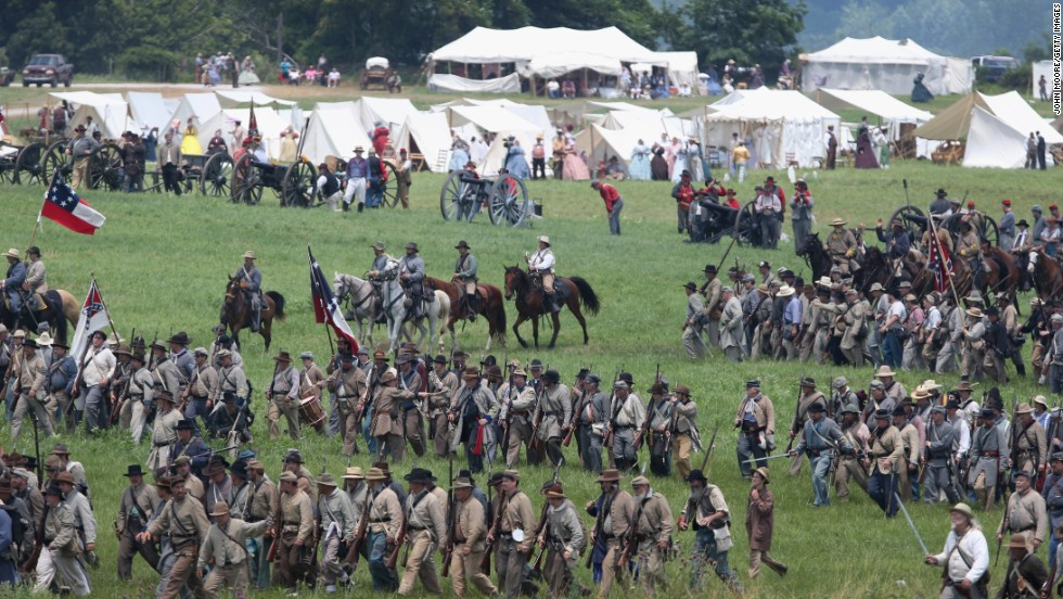 Confederate Civil War reenactors march towards Union positions during Pickett's Charge on June 30.