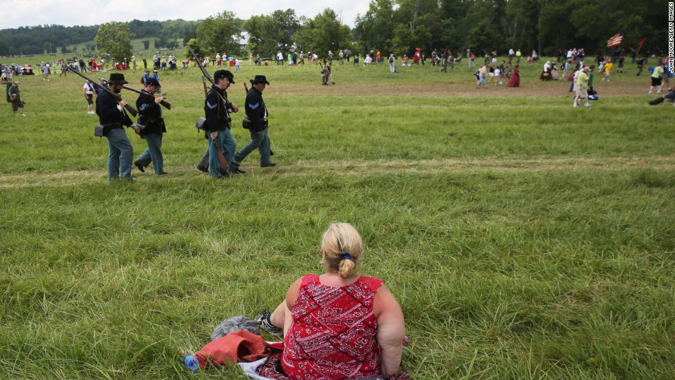 A spectator watches the event on June 30 from a seat on the grass.