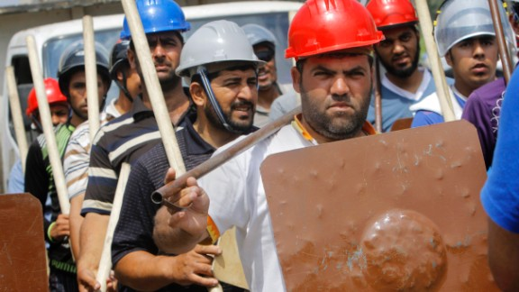 Supporters of President Morsy hold sticks and wear protective gear during training outside a mosque in Cairo on July 2.
