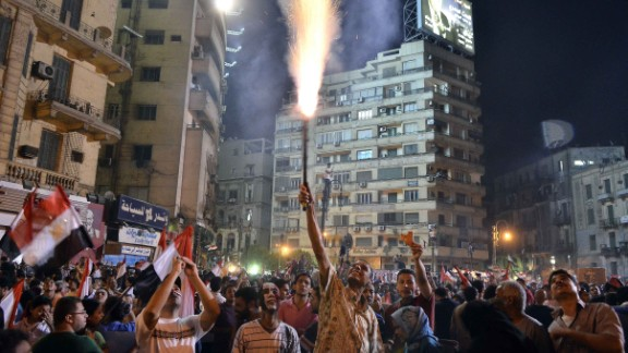 A protester lights a flare as hundreds of thousands of demonstrators gather in Cairo