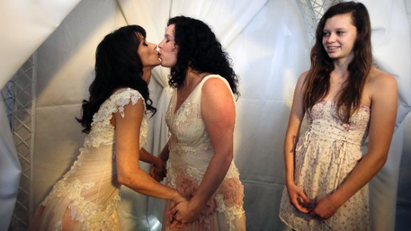 Andrea Taylor, left, and Sallee Taylor kiss during their wedding in West Hollywood, California, on Monday, July 1, as Sallee Taylor's daughter Grace Meier, right, looks on. The city of West Hollywood offered civil marriage ceremonies for same-sex couples free of charge Monday.