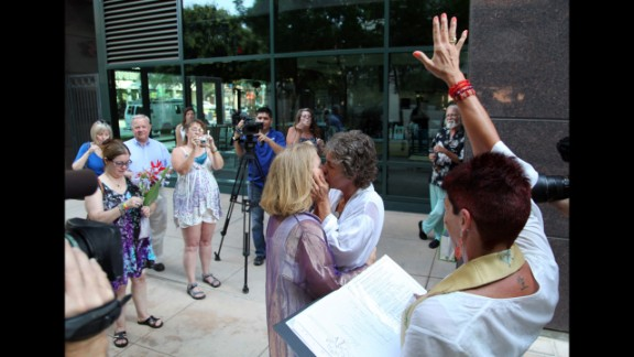Naomi Hendrix, right, and Rio Waller kiss right after they are pronounced married in Fresno on June 1.
