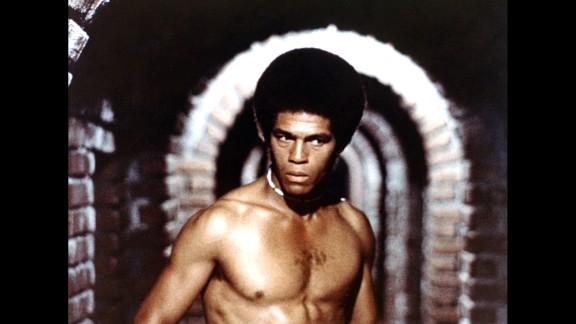 "in 1977's <a href=""http://www.imdb.com/title/tt0074213/plotsummary?ref_=tt_ov_pl"" target=""_blank"" target=""_blank"">""Black Samurai,""</a> Kelly starred as Robert Sand, a tennis playing secret agent."