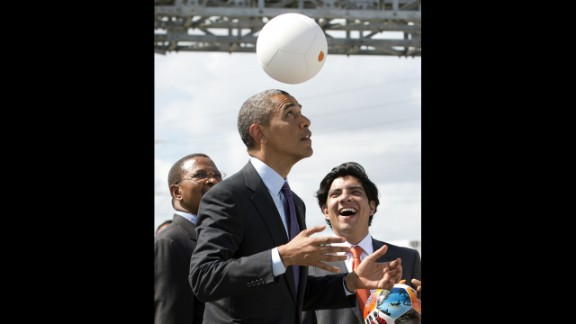 """Tanzania's president, left, watches as Obama plays with the energy-generating soccer ball at the Symbion Power Plant on July 2. """"I don't want to get too technical, but I thought it was pretty cool,"""" Obama said of the ball that harnesses kinetic energy to provide power."""