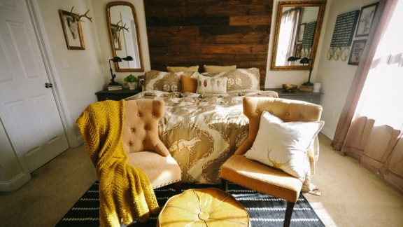 Liz Marie, an interior design student and blogger from North Carolina, teamed up with her husband to create a headboard that would be the focal point of their master bedroom. They built their floor-to-ceiling headboard from rustic boards that make a dramatic contrast against their cream bedroom walls.