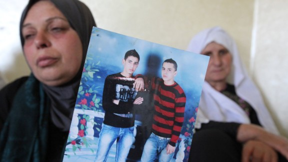 The mother of Muattazz Sharawanah holds up his photo (pictured R) prior to his funeral in Dura on Tuesday.