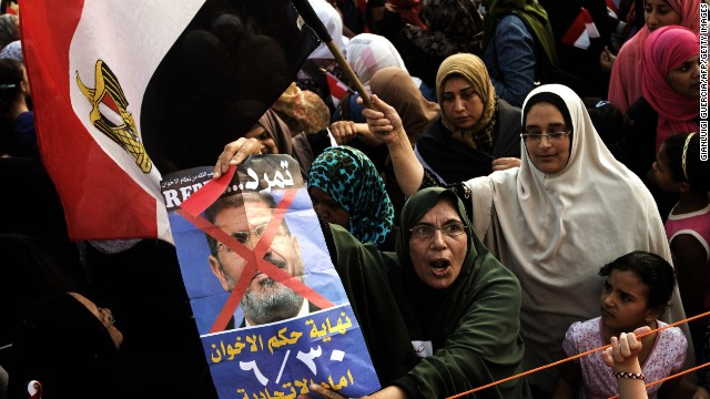 Opposition protesters shout slogans and show a defaced poster of their president as they gather in thousands at the Presidential Palace to protest against Egyptian President Mohamed Morsi and the Muslim Brotherhood on July 2, 2013 in Cairo.
