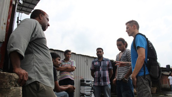 """Cosmo Beatson (far right), executive director of Vision First, a refugee aid organization, gives a pep talk to a group of Bangladeshi refugees in the slum village of Ping Che on June 25, 2013. """"When it dawns on refugees what they"""