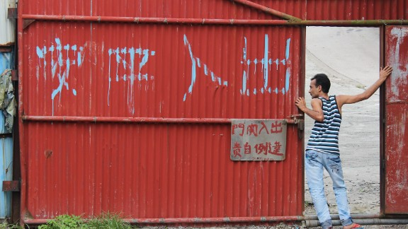 """Delwar, a refugee from Bangladesh, leans out of the main entrance of a housing compound in the slum village of Ping Che on June 25, 2013. The large Chinese characters read, """"Peace and safety to those who enter and leave."""""""
