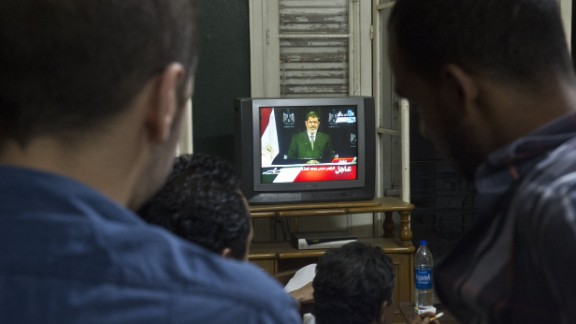 People watch Morsy on television in Cairo on Tuesday, July 2.